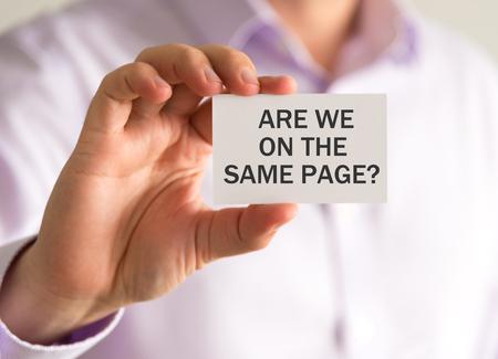 카드를 들고 사업가에 근접 촬영은 우리가 동일한 페이지에 있습니까? 메시지, 소프트 포커스 배경 및 빈티지 톤 비즈니스 개념 이미지