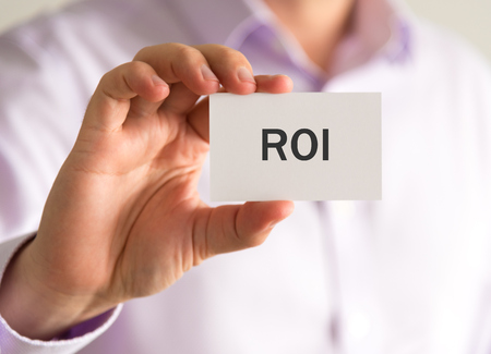 Closeup on businessman holding a card with ROI Return On Investment message, business concept image with soft focus background and vintage tone Stock Photo