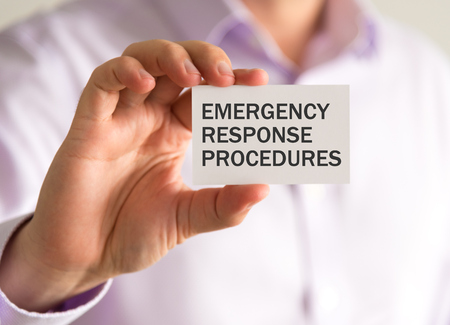 Closeup on businessman holding a card with ERP EMERGENCY RESPONSE PROCEDURES message, business concept image with soft focus background and vintage tone Stock Photo