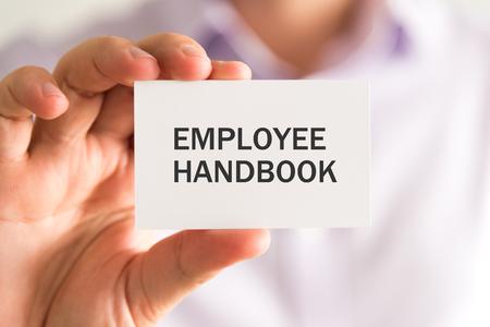 Close-up op zakenman die een kaart met MEDEWERKERShandboekbericht houden, bedrijfsconceptenbeeld met zachte nadrukachtergrond en uitstekende toon Stockfoto