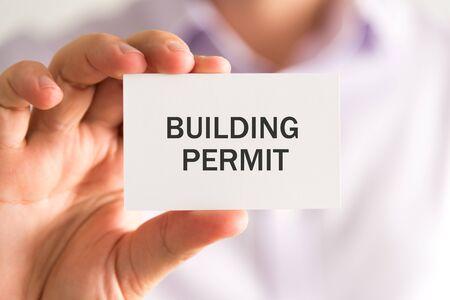 建築許可のメッセージ カード、ソフト フォーカスの背景とビンテージ トーン ビジネス コンセプト イメージを保持しているビジネスマンへのクロ