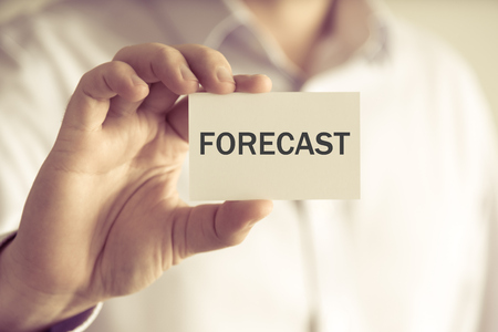 Closeup on businessman holding a card with text FORECAST , business concept image with soft focus background and vintage tone