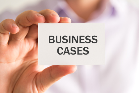 advise: Closeup on businessman holding a card with BUSINESS CASES message, business concept image with soft focus background Stock Photo