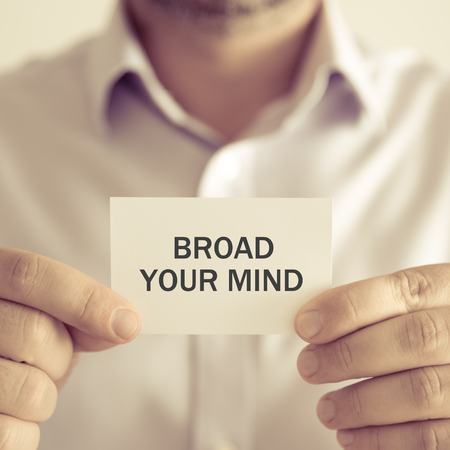 Closeup on businessman holding a card with text BROAD YOUR MIND, business concept image with soft focus background and vintage tone Stock Photo