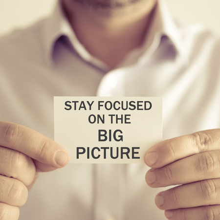 Closeup on businessman holding a card with text STAY FOCUSED ON THE BIG PICTURE, business concept image with soft focus background and vintage tone