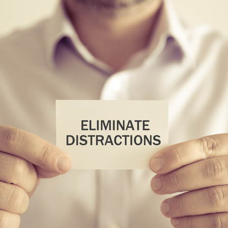 distractions: Closeup on businessman holding a card with text ELIMINATE DISTRACTIONS, business concept image with soft focus background and vintage tone Stock Photo