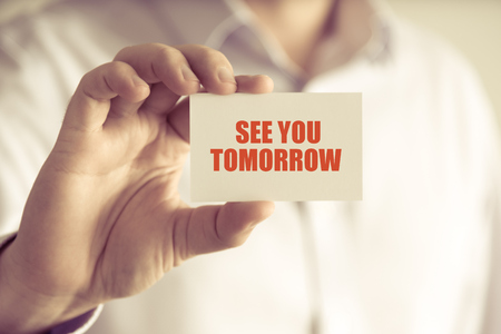 Closeup on businessman holding a card with text SEE YOU TOMORROW, business concept image with soft focus background and vintage tone