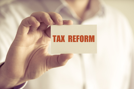 Closeup on businessman holding a card with text TAX REFORM, business concept image with soft focus background and vintage tone