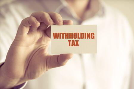 Closeup on businessman holding a card with text WITHHOLDING TAX, business concept image with soft focus background and vintage tone