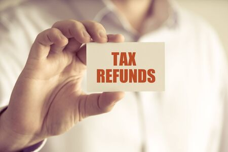 refunds: Closeup on businessman holding a card with text TAX REFUNDS, business concept image with soft focus background and vintage tone