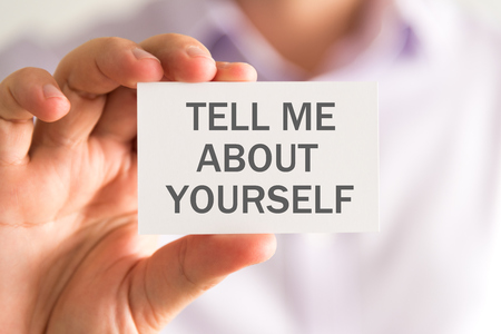 Closeup on businessman holding a card with TELL ME ABOUT YOURSELF message, business concept image with soft focus background