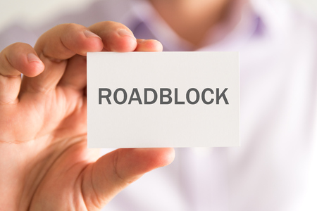 Closeup on businessman holding a card with ROADBLOCK message, business concept image with soft focus background Stock Photo