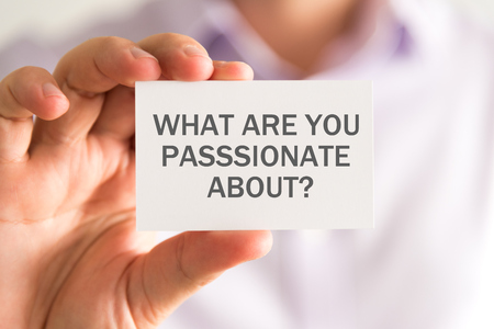 about you: Closeup on businessman holding a card with WHAT ARE YOU PASSIONATE ABOUT ? message, business concept image with soft focus background