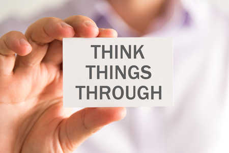 Closeup on businessman holding a card with THINK THINGS THROUGH message, business concept image with soft focus background Stock Photo