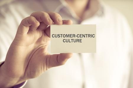 本文顧客中心の文化、ビジネス コンセプト イメージ ソフト フォーカスの背景とヴィンテージの口調でカードを持っている実業家でクローズ アップ