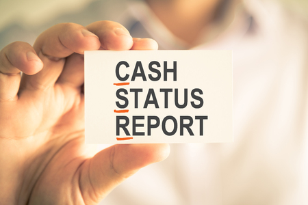 Closeup on businessman holding card with CSR CASH STATUS REPORT acronym text, business concept image with soft focus background and vintage tone