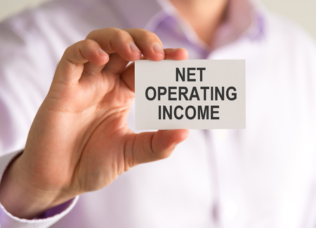 Closeup on businessman holding a card with NET OPERATING INCOME message, business concept image with soft focus background Stock Photo