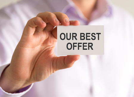 Closeup on businessman holding a card with OUR BEST OFFER message, business concept image with soft focus background