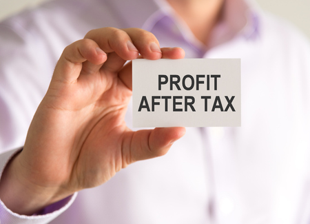 Closeup on businessman holding a card with PROFIT AFTER TAX message, business concept image with soft focus background
