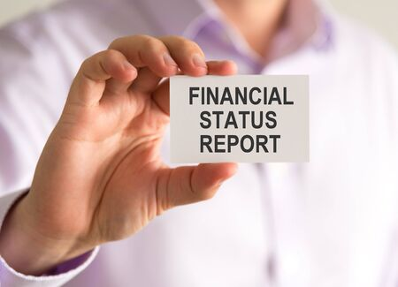 Closeup on businessman holding a card with FINANCIAL STATUS REPORT message, business concept image with soft focus background Stock Photo