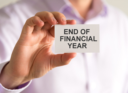 Closeup on businessman holding a card with END OF FINANCIAL YEAR message, business concept image with soft focus background