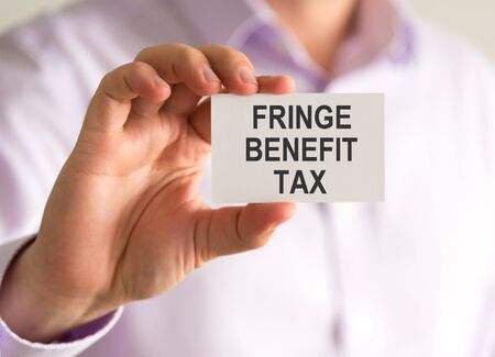 fringe benefit: Closeup on businessman holding a card with FRINGE BENEFIT TAX message, business concept image with soft focus background