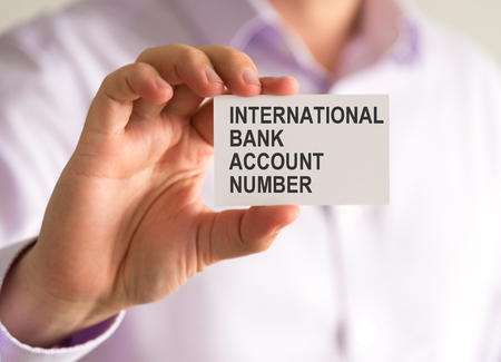 account executive: Closeup on businessman holding a card with IBAN INTERNATIONAL BANK ACCOUNT NUMBER message, business concept image with soft focus background