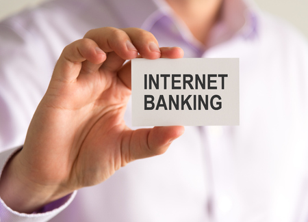 Closeup on businessman holding a card with INTERNET BANKING message, business concept image with soft focus background