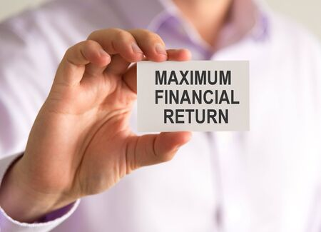 Closeup on businessman holding a card with MAXIMUM FINANCIAL RETURN message, business concept image with soft focus background