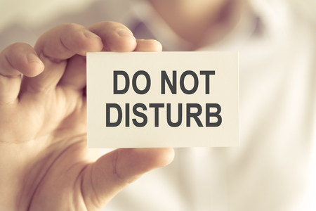 Closeup on businessman holding a card with text DO NOT DISTURB, business concept image with soft focus background and vintage tone