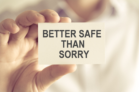 better safe than sorry: Closeup on businessman holding a card with text BETTER SAFE THAN SORRY, business concept image with soft focus background and vintage tone