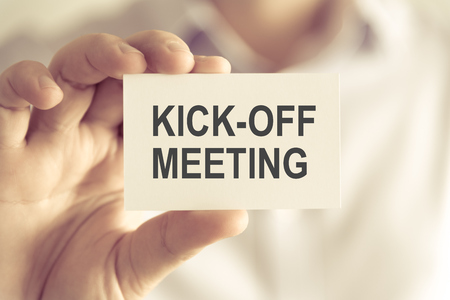 Closeup on businessman holding a card with text KICK-OFF MEETING, business concept image with soft focus background and vintage tone