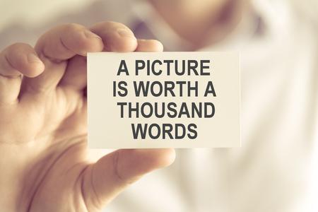 Nahaufnahme auf dem Geschäftsmann, der eine Karte mit Text hält Ein BILD WÜRDE TAUSEND WÖRTER, Geschäftskonzeptbild mit Hintergrund des weichen Fokus und Weinleseton