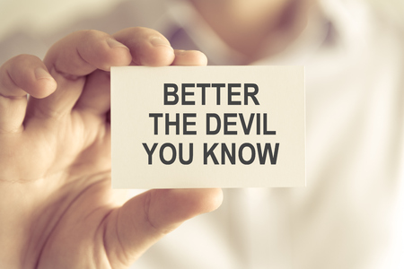 Closeup on businessman holding a card with text BETTER THE DEVIL YOU KNOW, business concept image with soft focus background and vintage tone