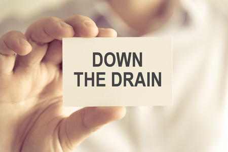 advise: Closeup on businessman holding a card with text DOWN THE DRAIN, business concept image with soft focus background and vintage tone