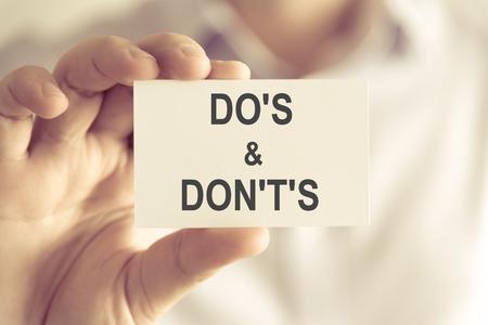 DOS と DONTS、ソフト フォーカスの背景とヴィンテージのトーンとビジネス コンセプト イメージのテキストとカードを持っている実業家でクローズ アップ 写真素材 - 74391126