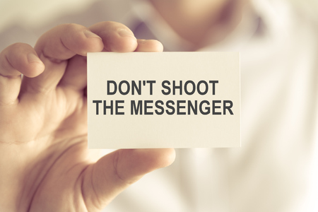 Closeup on businessman holding a card with text DONT SHOOT THE MESSENGER, business concept image with soft focus background and vintage tone