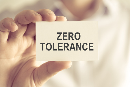 Closeup on businessman holding a card with text ZERO TOLERANCE, business concept image with soft focus background and vintage tone Stock Photo