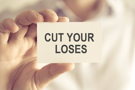 Closeup on businessman holding a card with text CUT YOUR LOSES, business concept image with soft focus background and vintage tone