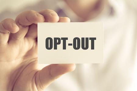 Close-up op zakenman die een kaart met tekst OPT-OUT, bedrijfsconceptbeeld houden met zachte nadrukachtergrond en uitstekende toon Stockfoto