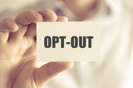 Closeup on businessman holding a card with text OPT-OUT, business concept image with soft focus background and vintage tone