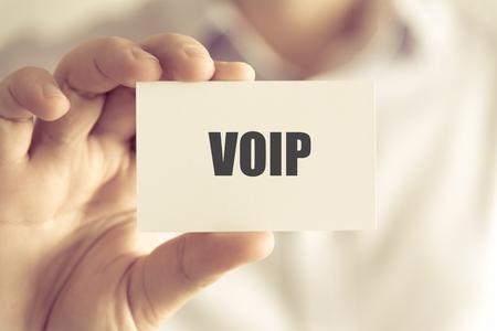 VOIP、ソフト フォーカスの背景とヴィンテージのトーンとビジネス コンセプト イメージのテキストとカードを持っている実業家でクローズ アップ 写真素材