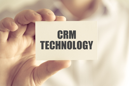 Closeup on businessman holding a card with text CRM TECHNOLOGY, business concept image with soft focus background and vintage tone Stock Photo
