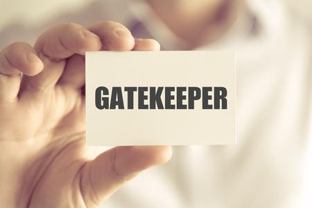 Nahaufnahme auf dem Geschäftsmann, der eine Karte mit Text GATEKEEPER, Geschäftskonzeptbild mit Hintergrund des weichen Fokus und Weinleseton hält Standard-Bild