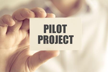 テキスト、ソフト フォーカスの背景とヴィンテージのトーンとビジネス コンセプト イメージのパイロット プロジェクトでカードを持っている実業 写真素材