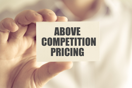 Closeup on businessman holding a card with text ABOVE COMPETITION PRICING, business concept image with soft focus background and vintage tone