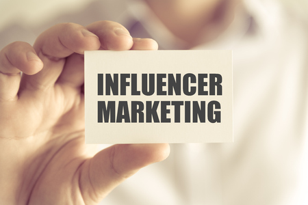 Closeup on businessman holding a card with text INFLUENCER MARKETING, business concept image with soft focus background and vintage tone