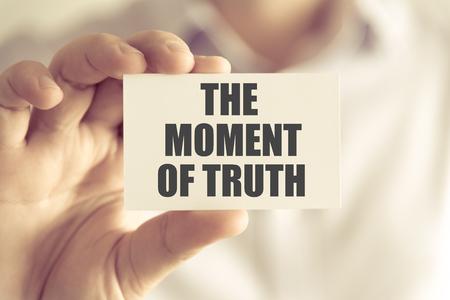 Nahaufnahme auf Unternehmer, die eine Karte mit Text die Stunde der Wahrheit, Business-Konzept Bild mit weichem Fokus Hintergrund und Vintage-Ton halten
