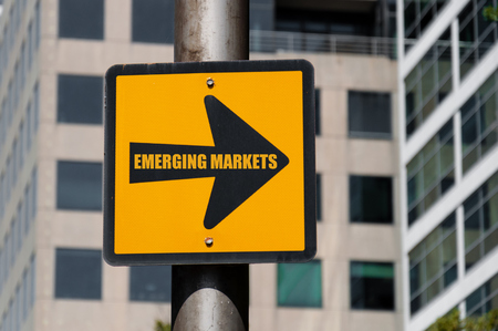Directional yellow sign with conceptual message EMERGING MARKETS on black arrow over defocused office building background.