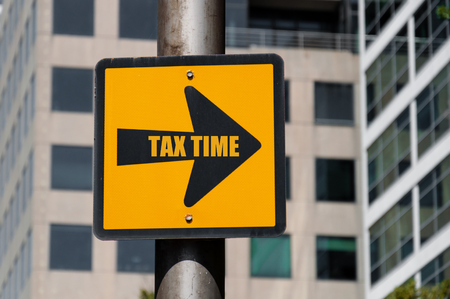 Directional yellow sign with conceptual message TAX TIME on black arrow over defocused office building background. Stock Photo